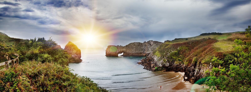 Όμορφο τοπίο της παραλίας και της ακτής με τα βουνά και τη βλάστηση Εντυπωσιακή σκηνή της ακτής και των απότομων βράχων Cantabria στοκ εικόνες