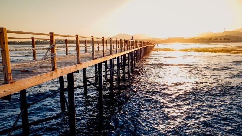 Όμορφο τοπίο των ήρεμων ωκεάνιων κυμάτων και της μακροχρόνιας ξύλινης αποβάθρας Καταπληκτικό ηλιοβασίλεμα aagainst λιμενοβραχιόνω στοκ φωτογραφία με δικαίωμα ελεύθερης χρήσης