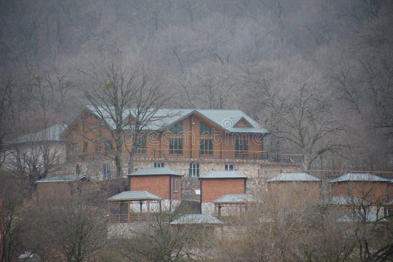 Όμορφο τοπίο των βουνών και του δάσους με το του χωριού κτήριο ή το παλαιό εγκαταλειμμένο σπίτι τούβλου Ομιχλώδες δασικό και παλα στοκ εικόνα με δικαίωμα ελεύθερης χρήσης