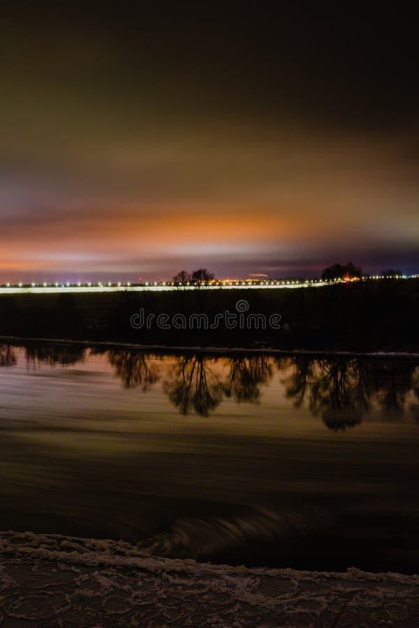 Όμορφο τοπίο χειμερινής νύχτας με τον ποταμό και την οδό lihgts στοκ φωτογραφίες