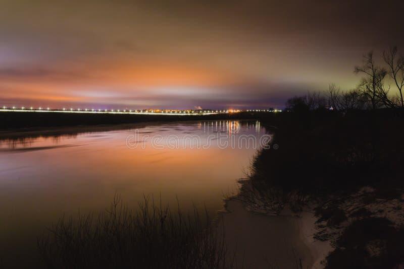 Όμορφο τοπίο χειμερινής νύχτας με τον ποταμό και την οδό lihgts στοκ εικόνες