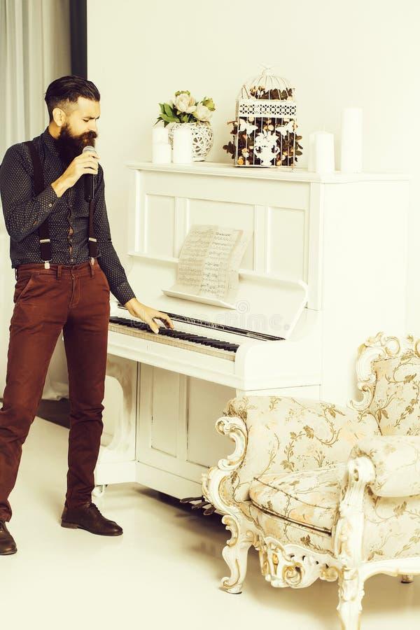 Όμορφο τραγούδι ατόμων κοντά στο πιάνο στοκ εικόνες
