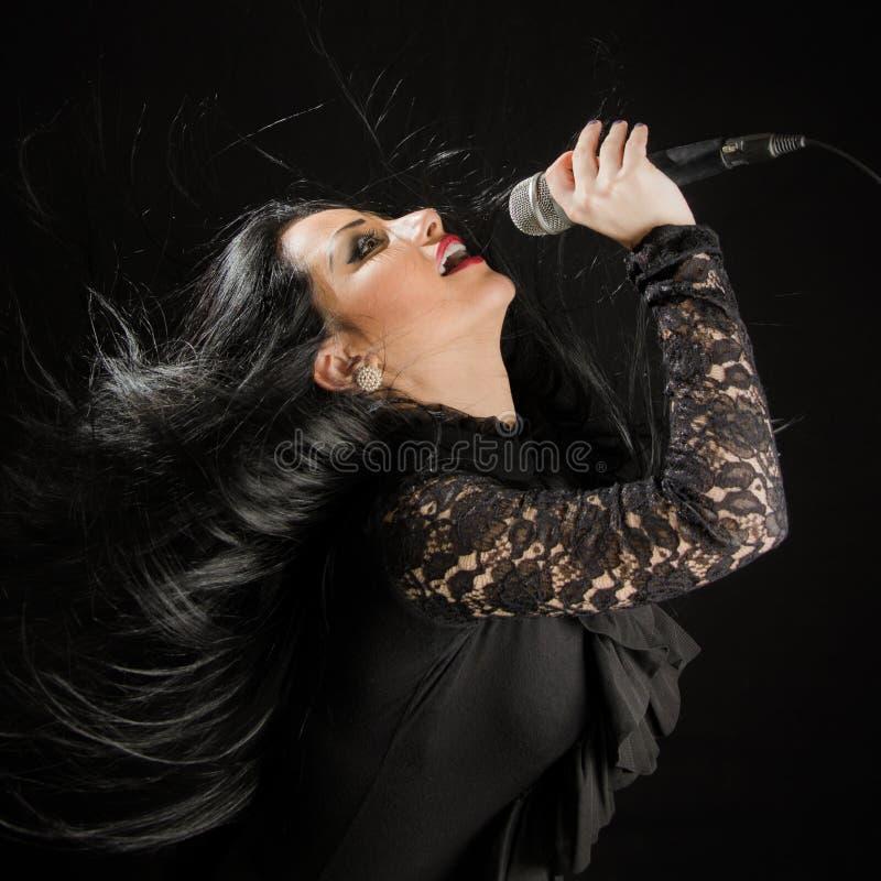 Όμορφο τραγούδι γυναικών με το μικρόφωνο στοκ εικόνες