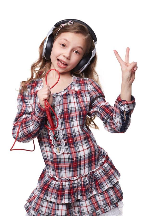 Όμορφο τραγούδι μικρών κοριτσιών στο φανταστικό μικρόφωνο στοκ εικόνες
