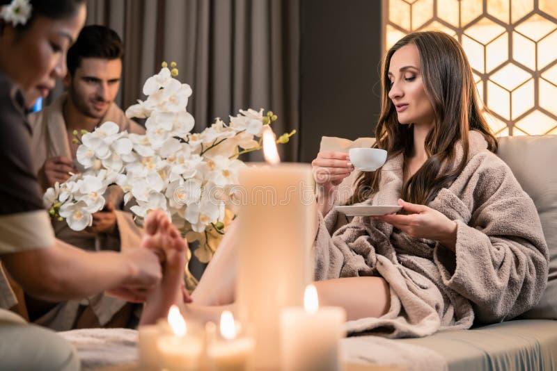 Όμορφο τσάι κατανάλωσης γυναικών κατά τη διάρκεια του θεραπευτικού μασάζ ποδιών στοκ φωτογραφία