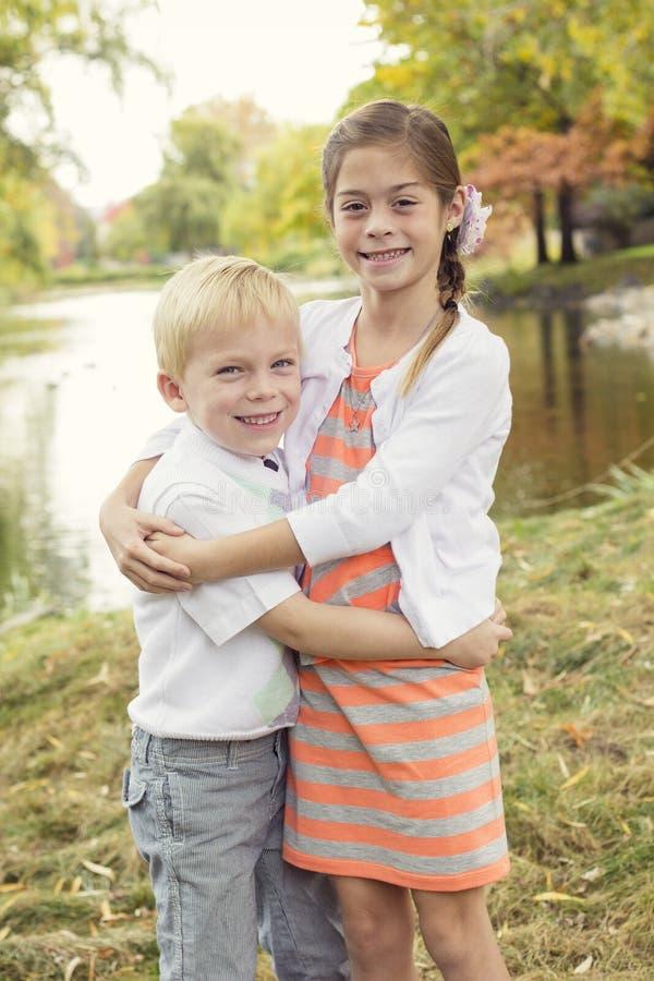 Όμορφο υπαίθριο πορτρέτο ενός χαριτωμένων αγοριού και ενός κοριτσιού στοκ εικόνα