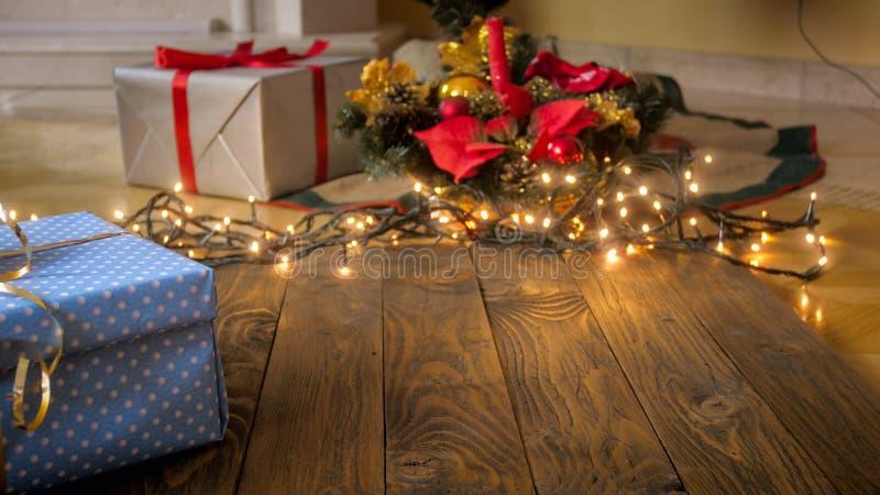 Όμορφο υπόβαθρο με τους ξύλινους πίνακες ενάντια στα φω'τα Χριστουγέννων πυράκτωσης, τα κιβώτια δώρων και τα μπιχλιμπίδια Τελειοπ στοκ εικόνες με δικαίωμα ελεύθερης χρήσης