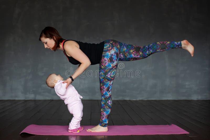 Όμορφο φίλαθλο κατάλληλο asana Virabhadrasana γιόγκας πρακτικών γυναικών που κρατά το μωρό της στοκ εικόνα