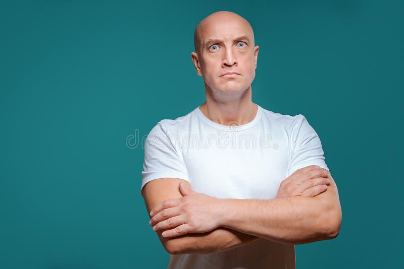 Όμορφο φαλακρό σοβαρό άτομο στην άσπρη μπλούζα στο μπλε υπόβαθρο στοκ φωτογραφία με δικαίωμα ελεύθερης χρήσης