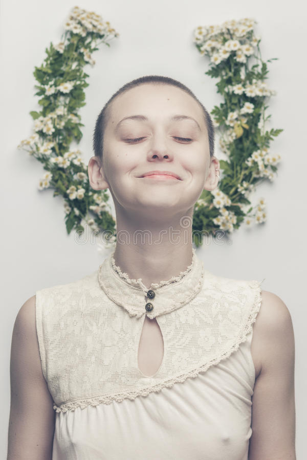 Όμορφο φαλακρό κορίτσι πέρα από το floral υπόβαθρο στοκ εικόνες
