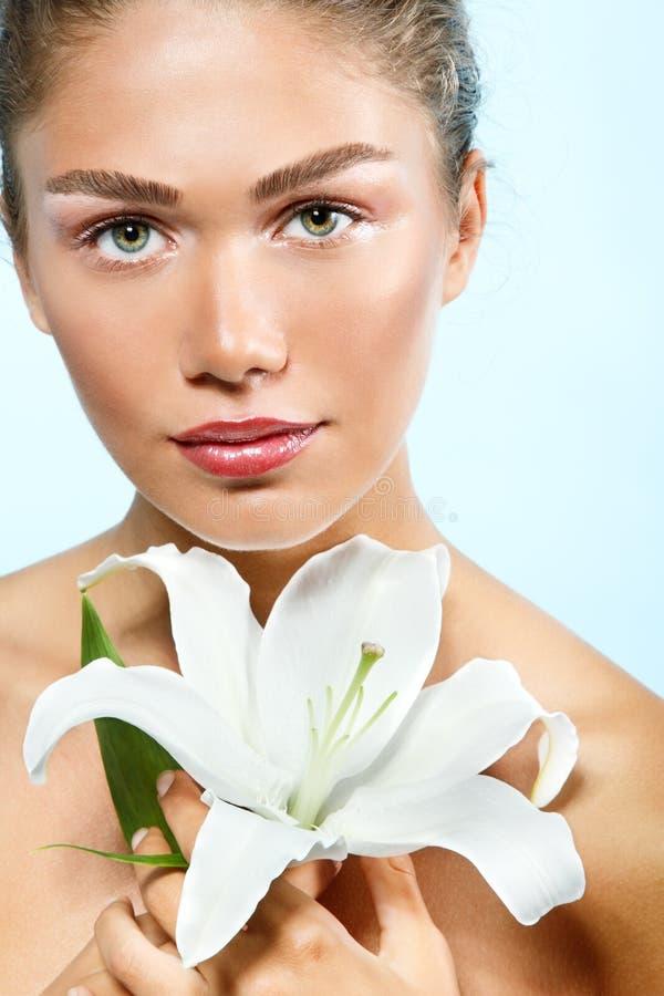 Όμορφο φρέσκο κορίτσι με το καθαρό λουλούδι κρίνων εκμετάλλευσης δερμάτων, isolat στοκ εικόνες