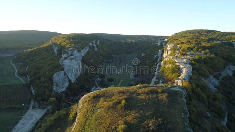 Όμορφο φυσικό τοπίο βουνών με τους φθινοπωρινούς λόφους, το νεφελώδη μπλε ουρανό και το φως του ήλιου αύξησης στο μουντό ορίζοντα στοκ εικόνες με δικαίωμα ελεύθερης χρήσης