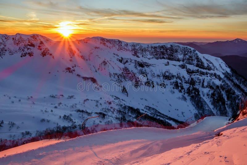 Όμορφο φυσικό τοπίο ηλιοβασιλέματος χειμερινών βουνών των χιονωδών βουνών Καύκασου και κλίση σκι του χιονοδρομικού κέντρου βουνών στοκ φωτογραφίες