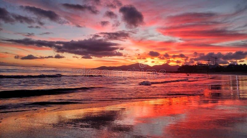 Όμορφο φωτεινό κόκκινο ηλιοβασίλεμα πέρα από τον Ατλαντικό Ωκεανό puerto del Carmen στο Κανάριο νησί Lanzarote στην Ισπανία στοκ φωτογραφία