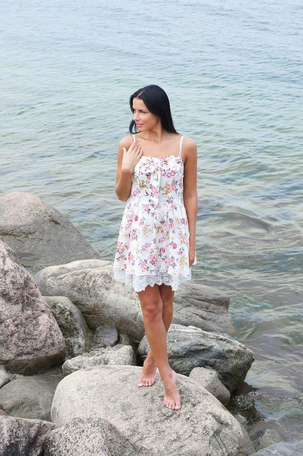 όμορφο φόρεμα κοντά στις νεολαίες γυναικών θάλασσας στοκ φωτογραφίες
