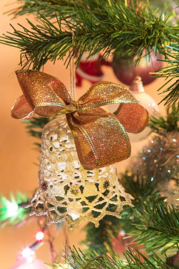 Όμορφο χέρι - γίνοντα κουδούνι με το τόξο στο χριστουγεννιάτικο δέντρο στοκ φωτογραφίες