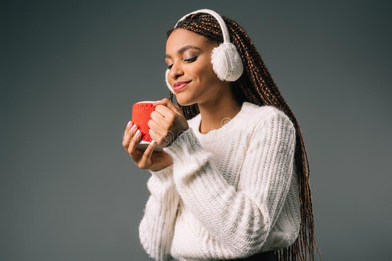όμορφο χαμογελώντας κορίτσι αφροαμερικάνων στα καλύμματα αυτιών γουνών που κρατά το φλυτζάνι με το καυτό ποτό στοκ φωτογραφία με δικαίωμα ελεύθερης χρήσης