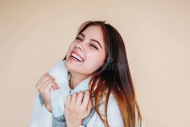 Όμορφο χαμογελώντας κορίτσι με το καθαρό δέρμα και σκοτεινό μακρυμάλλη στο άνετο άσπρο πουλόβερ και θερμό μαντίλι στο μπεζ υπόβαθ στοκ εικόνα