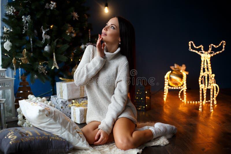 Όμορφο χαμογελώντας κορίτσι σε ένα άσπρο πουλόβερ κοντά στο δέντρο chrismas στοκ φωτογραφία