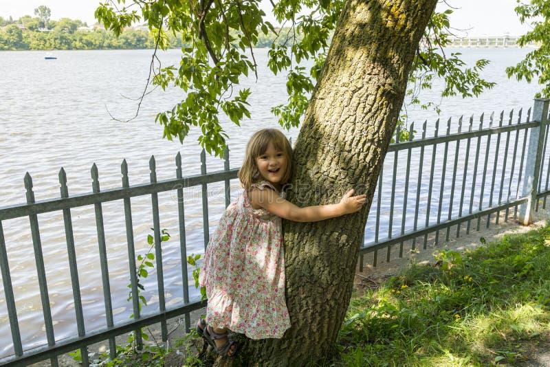 Όμορφο χαμογελώντας μικρό κορίτσι που αγκαλιάζει έναν κορμό δέντρων στοκ φωτογραφίες