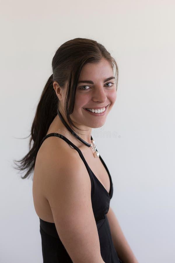 Όμορφο χαμογελώντας νέο κορίτσι brunette που φορά το μαύρα φόρεμα και το μαργαριτάρι βραδιού στοκ φωτογραφία με δικαίωμα ελεύθερης χρήσης