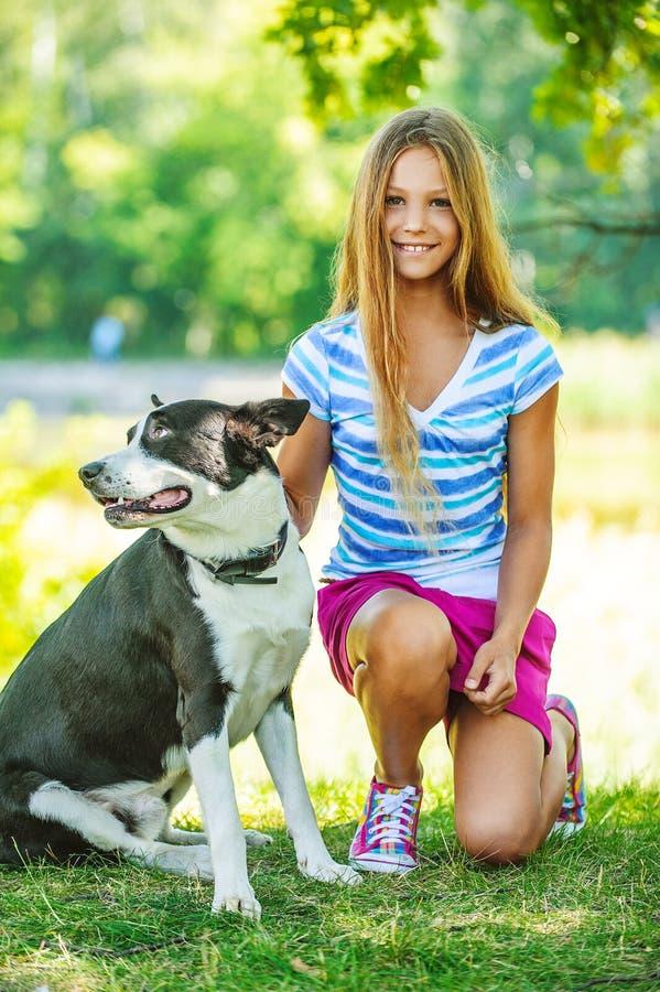 Όμορφο χαμογελώντας κορίτσι με το μαύρο σκυλί στοκ εικόνα