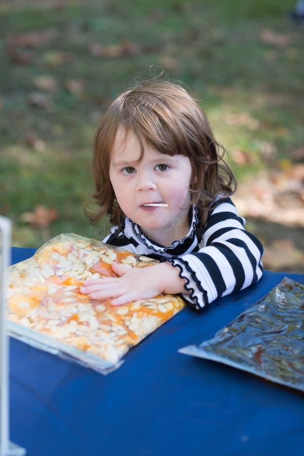 Όμορφο χαμογελώντας κορίτσι μικρών παιδιών που φορά τη γραπτή εξάρτηση αποκριών που αισθάνεται τους σπόρους κολοκύθας και που χαμ στοκ φωτογραφία