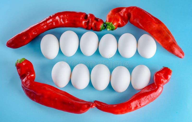 Όμορφο χαμόγελο από τα άσπρα αυγά και το κόκκινο πιπέρι Άσπρα δόντια, ευτυχής τρόπος ζωής στοκ εικόνες
