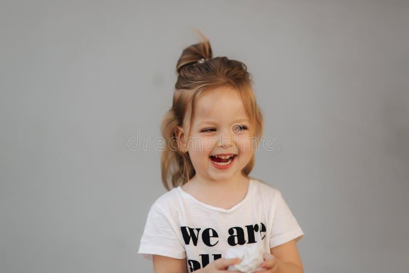 Όμορφο χαμόγελο μικρών κοριτσιών στη κάμερα Γκρίζα ανασκόπηση είμαστε όλα τα παιδιά στοκ φωτογραφία