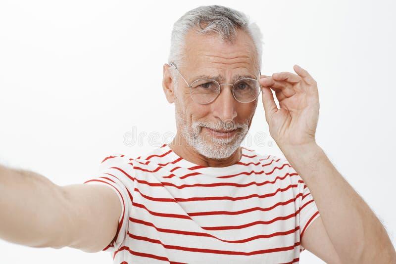 Όμορφο χαρισματικό ώριμο γενειοφόρο άτομο με την γκρίζα τρίχα στα γυαλιά και τη ριγωτή μπλούζα που τραβούν το χέρι για να κρατήσε στοκ φωτογραφία