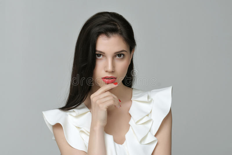 Όμορφο χαριτωμένο κορίτσι που φορά ένα άσπρο φόρεμα ενάντια σε ένα γκρίζο backgro στοκ εικόνες