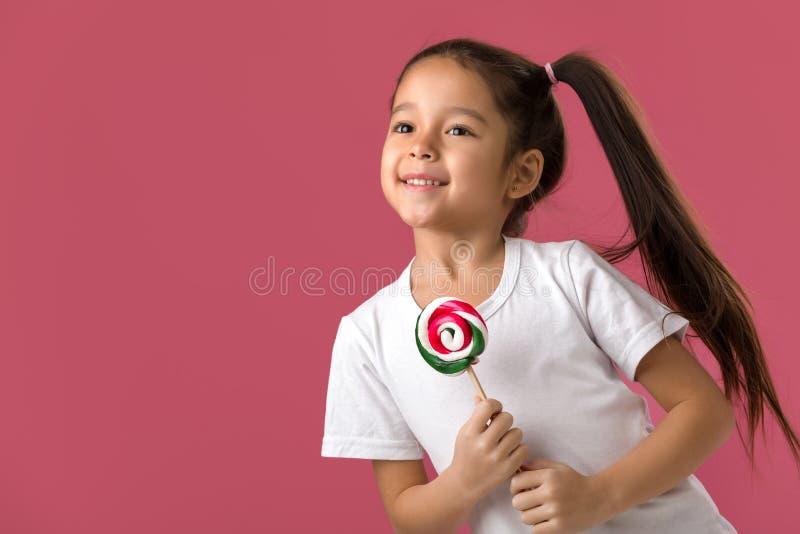 Όμορφο χαριτωμένο μικρό κορίτσι με ένα lollipop στοκ εικόνα