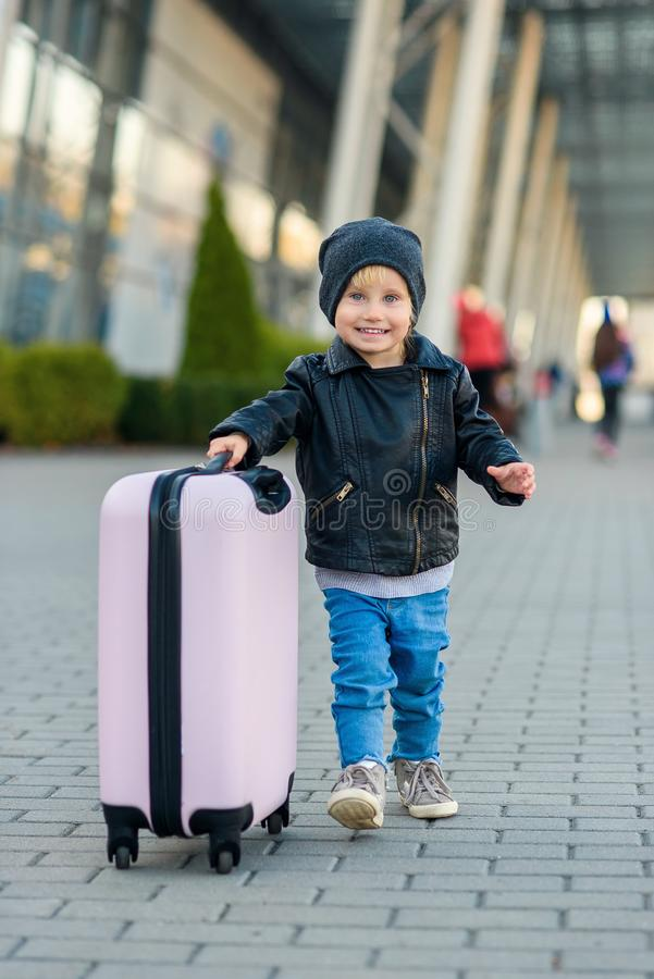 Όμορφο χαρούμενο κορίτσι ταξιδεύει με κομψή βαλίτσα Ένα μικρό παιδί ταξιδεύει στο ταξίδι από το αεροδρόμιο στοκ εικόνες