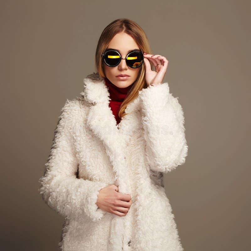 Όμορφο χειμερινό κορίτσι στην άσπρα γούνα και τα γυαλιά ηλίου όμορφο κορίτσι μόδας ανασκόπησης που απομονώνεται άσπρος χειμώνας 1 στοκ εικόνα