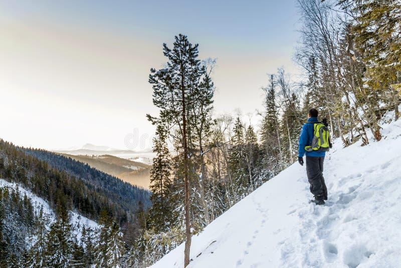 Όμορφο χειμερινό τοπίο στα βουνά και τον οδοιπόρο νεαρών άνδρων στοκ φωτογραφίες