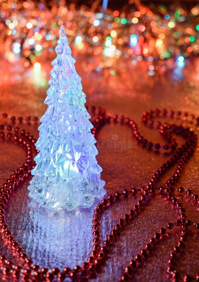 Όμορφο χριστουγεννιάτικο δέντρο γυαλιού σε ένα υπόβαθρο των φω'των στοκ εικόνα