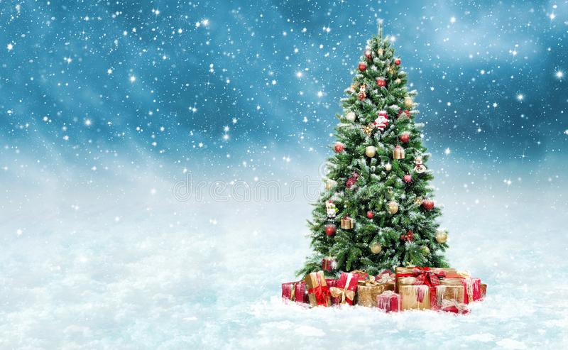 Όμορφο χριστουγεννιάτικο δέντρο με τα χρυσά και κόκκινα παρόντα κιβώτια σε ένα χιονώδες χειμερινό τοπίο στοκ φωτογραφία