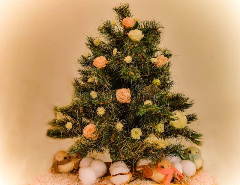 Όμορφο χριστουγεννιάτικο δέντρο, που διακοσμείται με τα φρέσκα λουλούδια και τα εορταστικά σπινθηρίσματα στοκ εικόνα