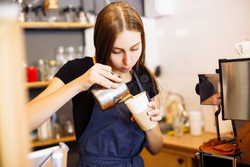 Όμορφο χύνοντας γάλα barista στο φλιτζάνι του καφέ στη καφετερία στοκ εικόνες