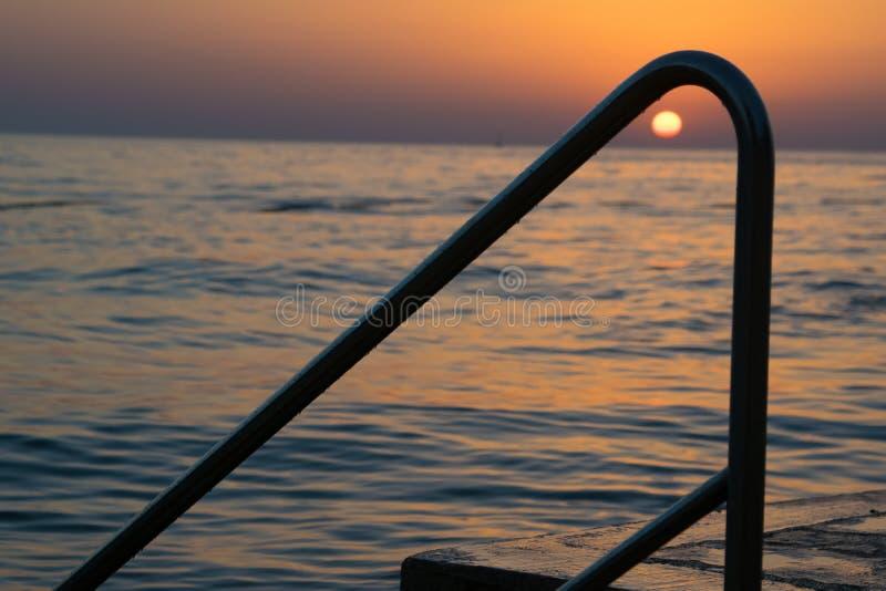 Όμορφο ωκεάνιο ηλιοβασίλεμα με τη σκιαγραφία στοκ εικόνα