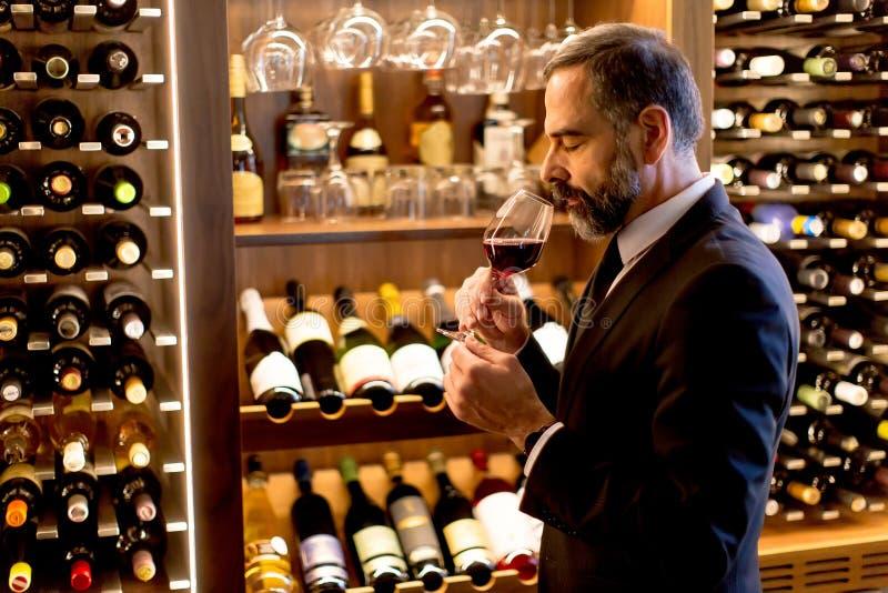 Όμορφο ώριμο άτομο που δοκιμάζει το κόκκινο κρασί στοκ εικόνες