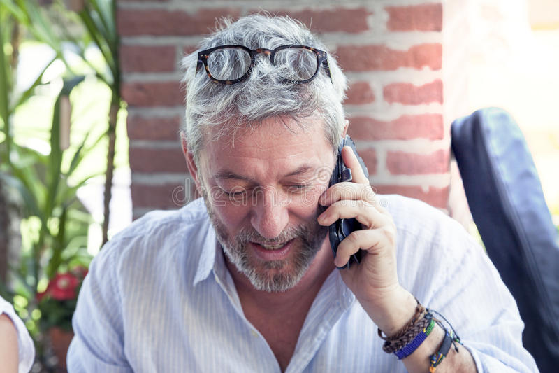 Όμορφο ώριμο άτομο που μιλά στο τηλέφωνο στοκ φωτογραφία