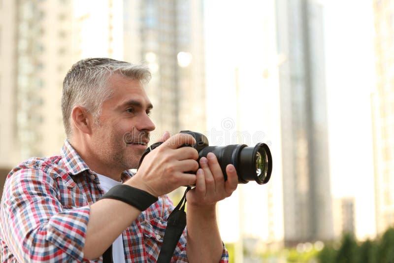 Όμορφο ώριμο άτομο που παίρνει τη φωτογραφία με την επαγγελματική κάμερα υπαίθρια στοκ εικόνα
