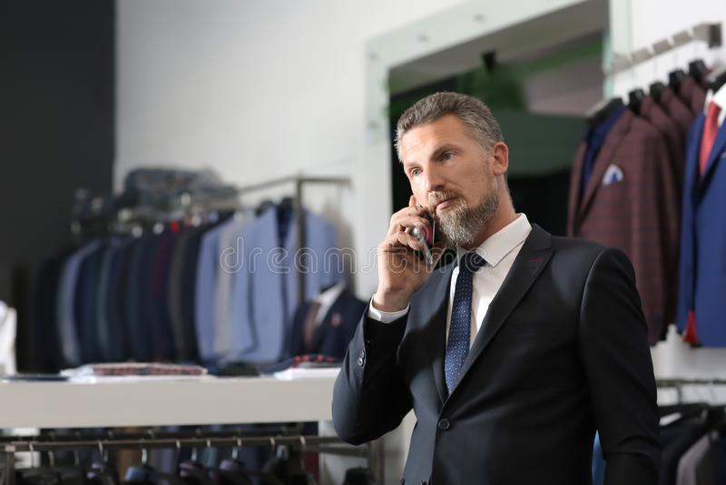 Όμορφο ώριμο άτομο στο μοντέρνο κοστούμι που μιλά στο κινητό τηλέφωνο στο menswear κατάστημα στοκ εικόνες