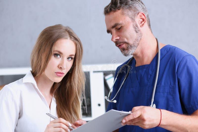 Όμορφο ώριμο μαξιλάρι προσφοράς γιατρών που υπογράφει με την ασημένια μάνδρα στοκ εικόνες