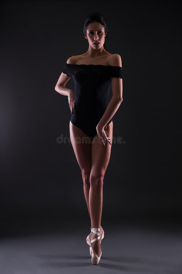 Όμορφο ballerina γυναικών στη μαύρη τοποθέτηση κοστουμιών σωμάτων στα toe στοκ εικόνες