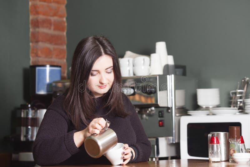 Όμορφο barista γυναικών που κάνει το cappuccino στοκ φωτογραφία