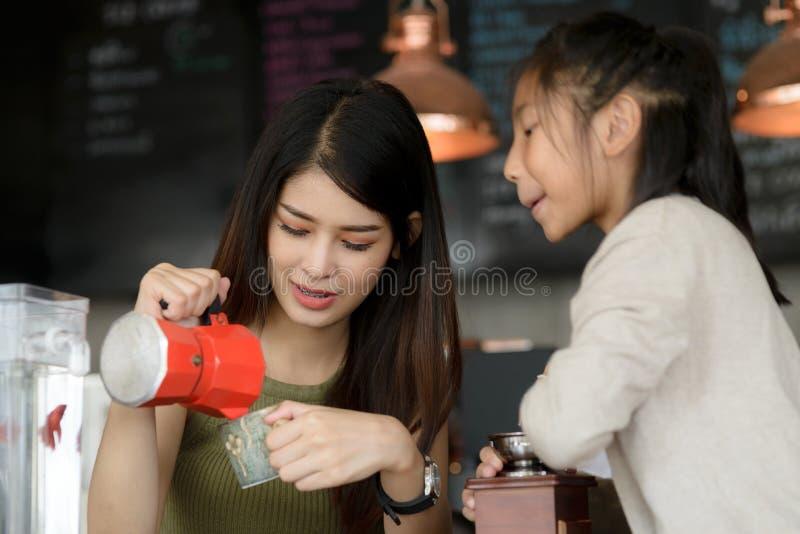 Όμορφο barista που διδάσκει την αδελφή της πώς να κάνει τον καφέ στοκ εικόνες