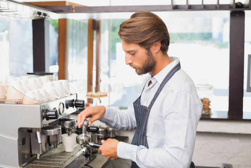 Όμορφο barista που κατασκευάζει ένα φλιτζάνι του καφέ στοκ εικόνα