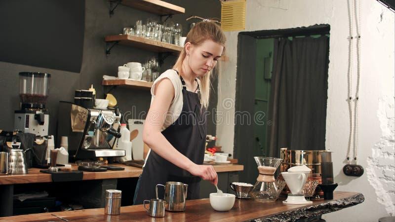 Όμορφο barista που κατασκευάζει τον καφέ στον καφέ, που χύνει το γάλα σε ένα φλυτζάνι στοκ φωτογραφίες με δικαίωμα ελεύθερης χρήσης